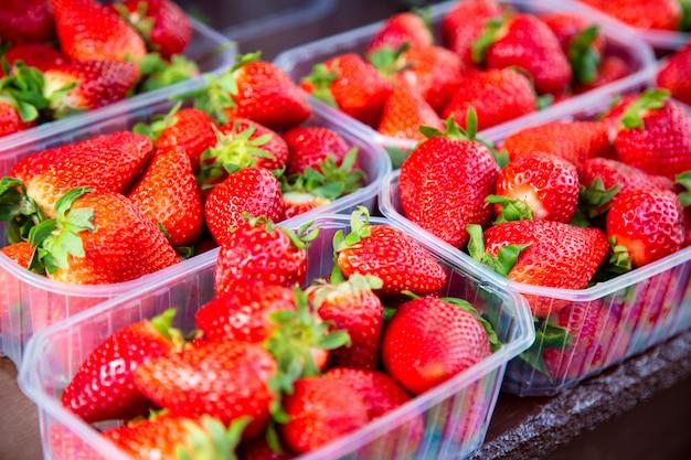 Muitos morangos frescos em caixas para venda em um mercado de frutas ao ar livre