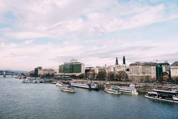 Muitos navios navegando no rio danúbio, em budapeste, tendo como pano de fundo um céu azul nublado Foto Premium