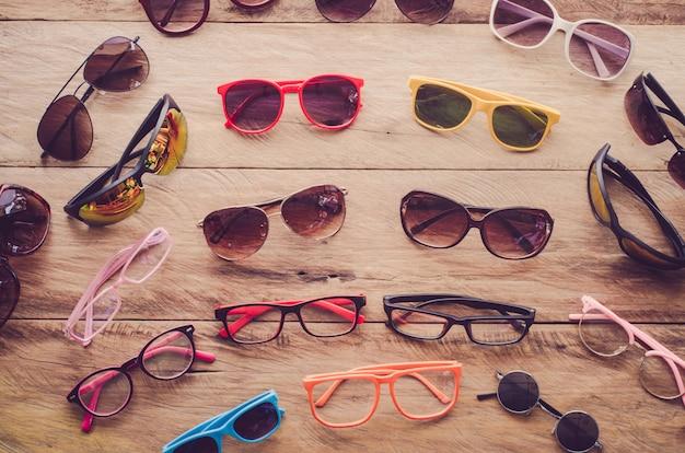 Muitos óculos de sol moda e óculos na madeira