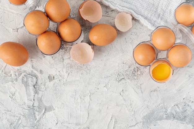 Muitos ovos crus de frango cru em uma bandeja de plástico na mesa de grunge, dietas especiais de ovo