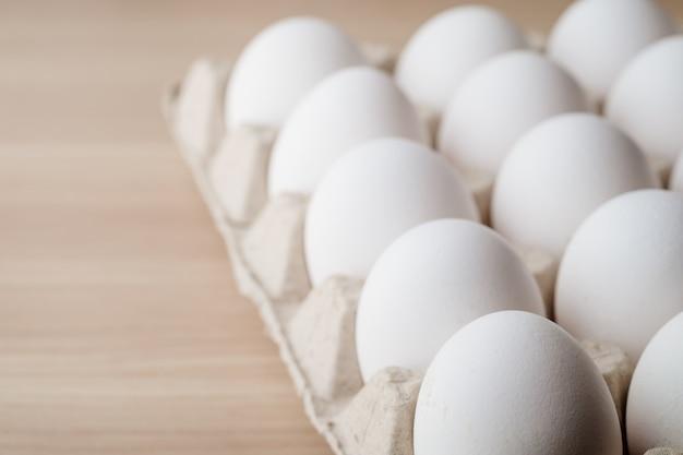 Muitos ovos de galinha branca comida em caixa de bandeja