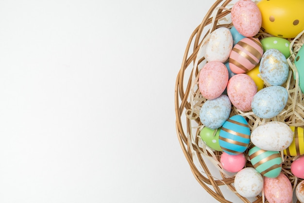 Muitos ovos de páscoa coloridos em uma cesta em branco