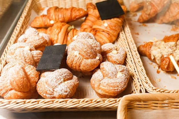 Muitos pães e croissants em uma prateleira de uma padaria