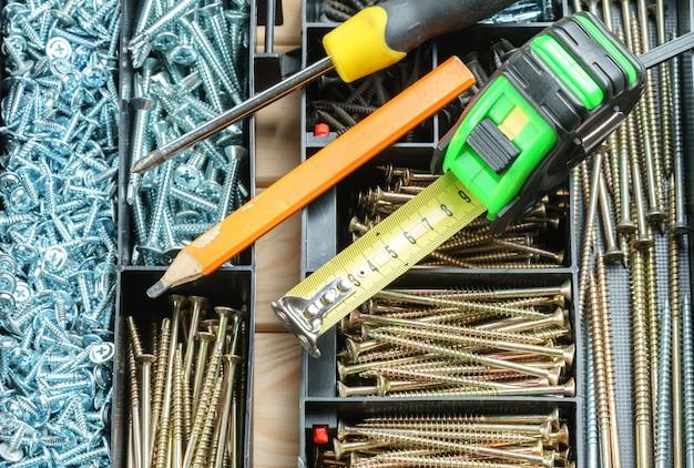 Muitos parafusos na caixa de organizador de plástico, ferramentas de trabalho