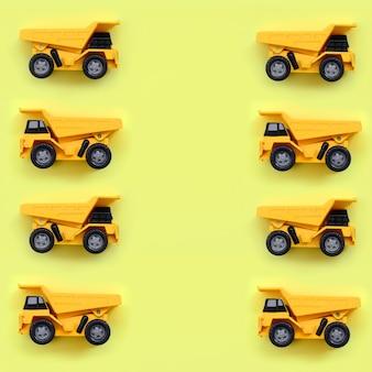 Muitos pequenos caminhões de brinquedo amarelo sobre fundo de textura de cor amarela pastel de moda