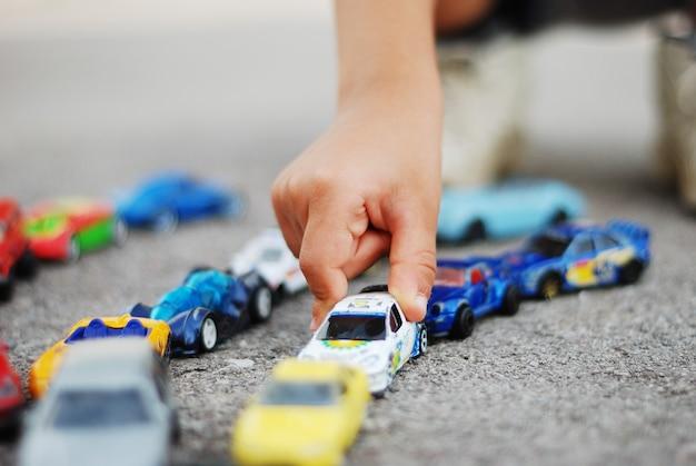 Muitos pequenos carros no chão e criança está brincando com