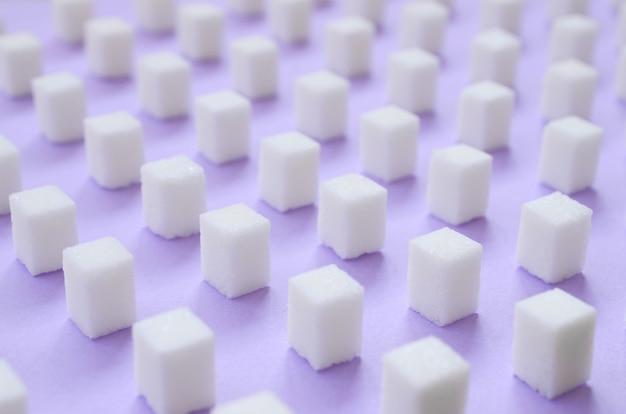 Muitos pequenos cubos de açúcar estão alinhados em um fundo violeta.