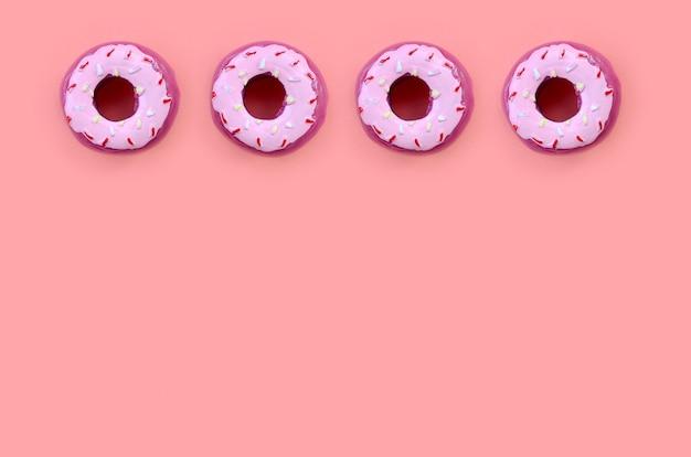 Muitos pequenos donuts de plástico encontra-se em um colorido pastel. flat lay mínimo. vista do topo