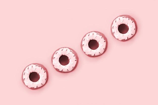 Muitos pequenos donuts de plástico encontra-se em um fundo colorido pastel