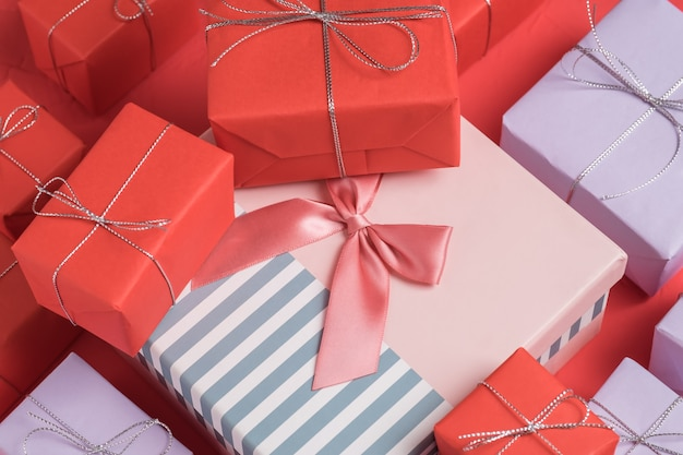 Muitos pequenos presentes misturados embrulhados em papel vermelho e lilás