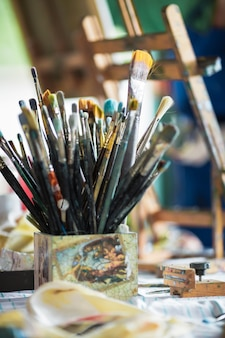 Muitos pincéis de pintura diferentes na área de trabalho do artista