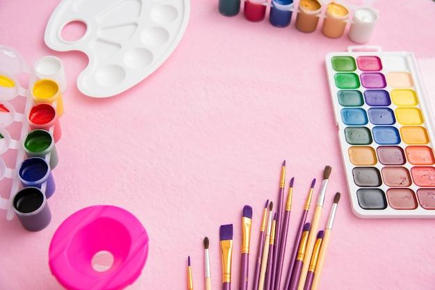 Muitos pincéis diferentes para desenhar com guache e paleta em um fundo rosa.