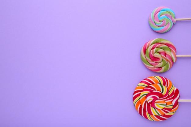 Muitos pirulitos coloridos no fundo roxo, doces