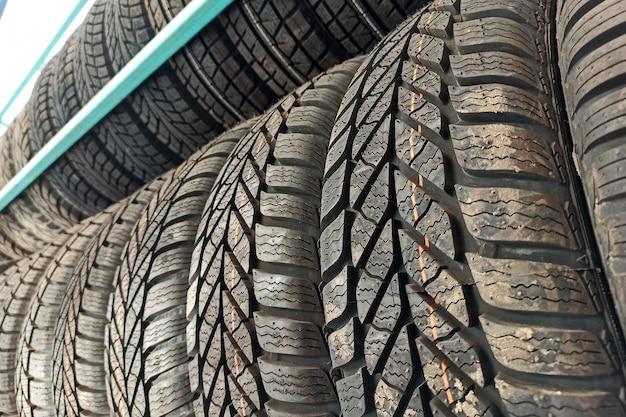 Muitos pneus de borracha preta para carros na prateleira da loja para venda.