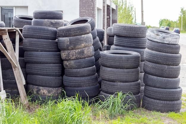 Muitos pneus de carros usados velhos empilhados uns em cima dos outros na grama perto da estrada perto da loja de pneus