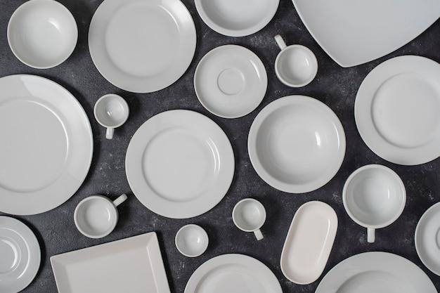 Muitos prato de cerâmica vazio branco e copo em fundo preto, close-up. vista de cima
