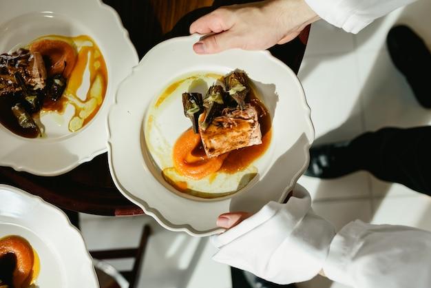 Muitos pratos de carne de porco confit com alcachofras e molho suculento servido por garçons em um restaurante de luxo.