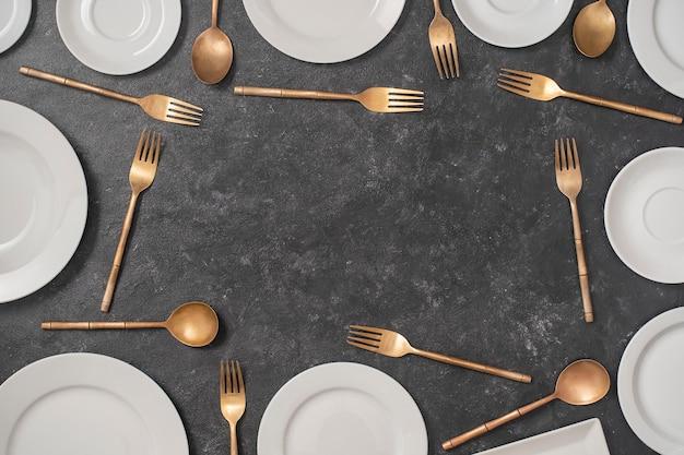 Muitos pratos de cerâmica brancos e garfos e colheres de latão em fundo preto