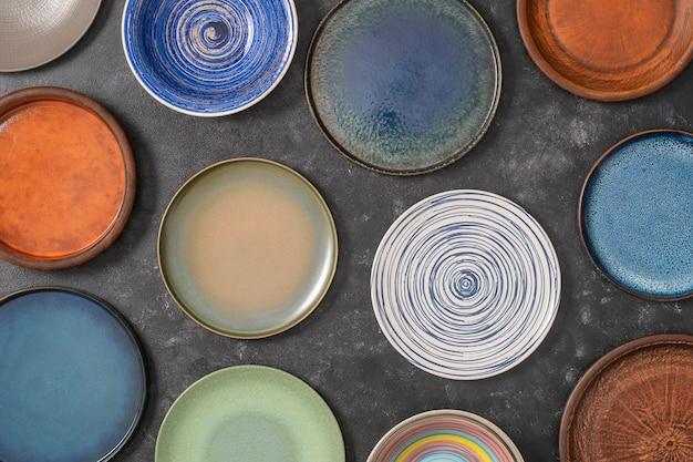 Muitos pratos de cerâmica vazios coloridos em fundo preto, close-up