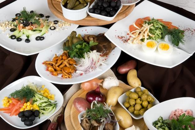 Muitos pratos de comida na mesa do restaurante. fim do prato da salada acima.