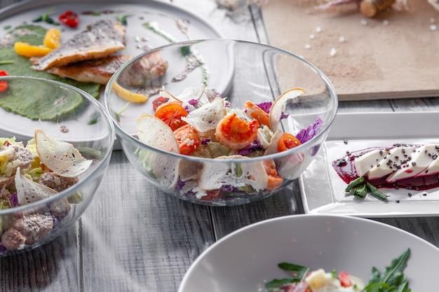 Muitos pratos diferentes, peixe, saladas serviram na mesa do restaurante.