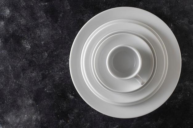 Muitos pratos e copos de cerâmica vazios brancos em fundo preto