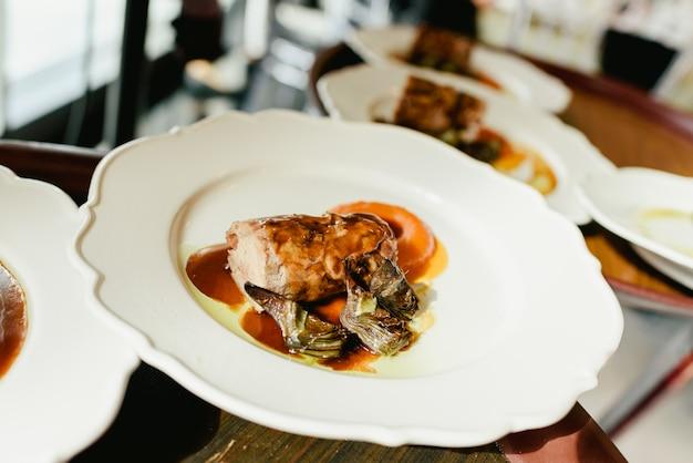Muitos pratos lombo de porco confit com alcachofras e molho suculento servido por garçons