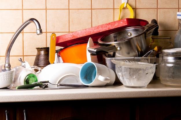 Muitos pratos sujos estão na pia da cozinha que precisa ser lavada.