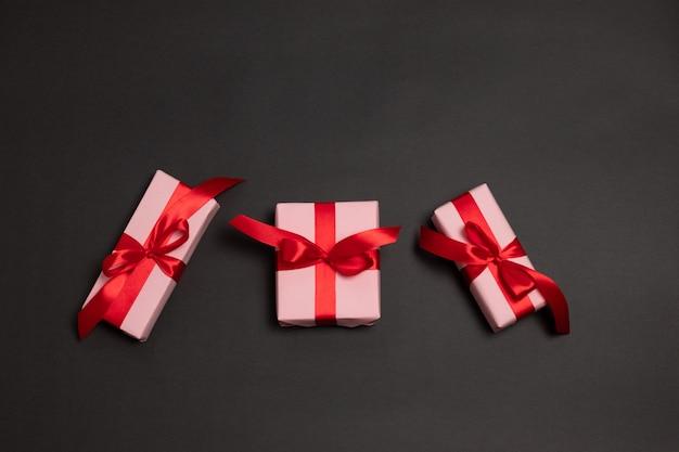 Muitos presentes de surpresa grande embrulhados com laço de fita vermelha sobre um fundo escuro.