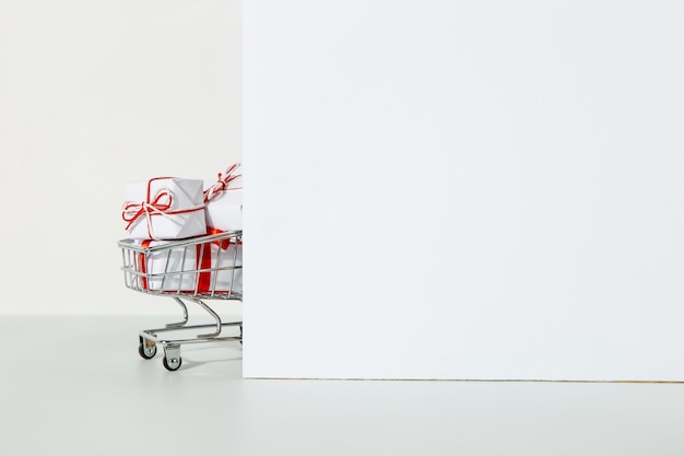 Muitos presentes no carrinho de compras em um branco.