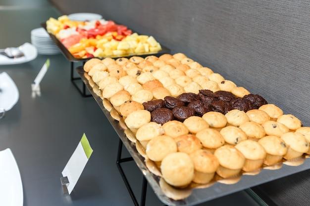 Muitos queques doces e frutos cortados em uma tabela em uma ruptura de café no escritório.