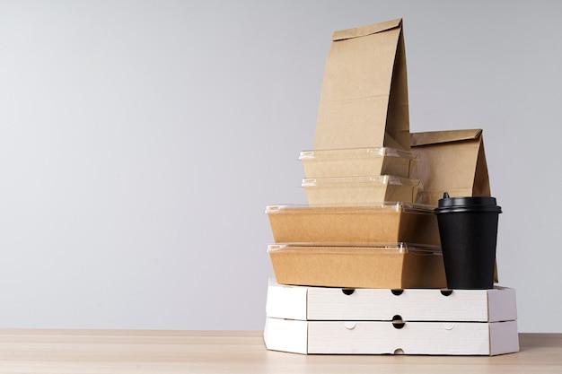 Muitos recipientes de comida para viagem, caixa de pizza, xícaras de café e sacos de papel em fundo cinza claro. entrega de alimentos