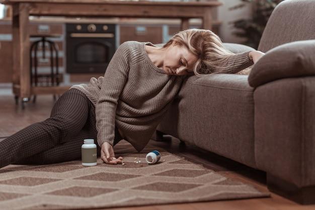 Muitos remédios. mulher loira com suéter marrom caindo no chão depois de tomar muitos remédios