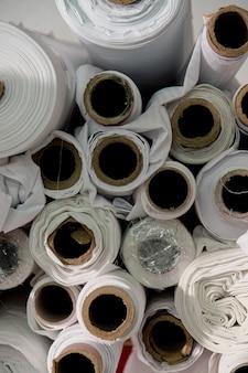 Muitos rolos de tecido branco em um estúdio de alfaiate