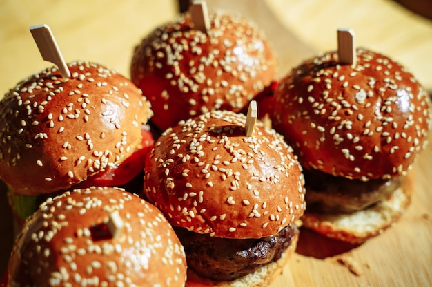 Muitos saborosos hambúrgueres na mesa de madeira