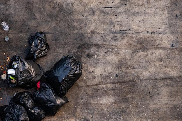 Muitos sacos de lixo pretos amarrados na calçada