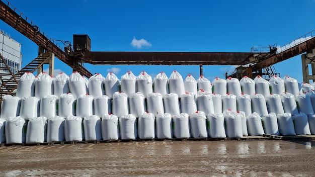Muitos sacos grandes brancos com fertilizantes químicos em um armazém ao ar livre pilha de sacos em uma fileira
