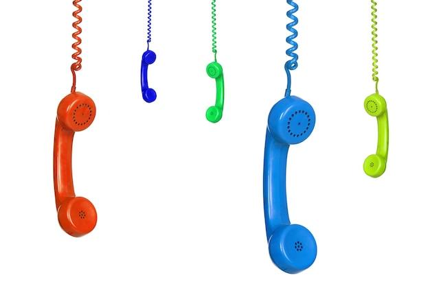 Muitos telefones antigos coloridos pendurados isolados em um fundo branco