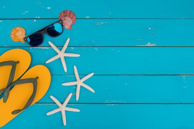 Muitos tipos de conchas, óculos escuros e estrelas do mar sobre fundo azul de madeira rústica.