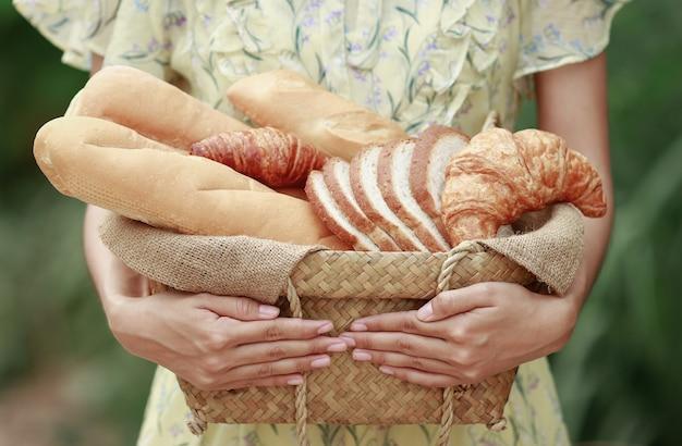 Muitos tipos de pão de padaria para uma alimentação saudável com a menina segurando