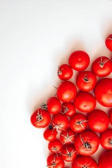 Muitos tomates vermelhos maduros estão espalhados na mesa