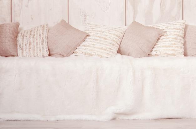 Muitos travesseiros estão no sofá, que é coberto com um grande véu de pelúcia