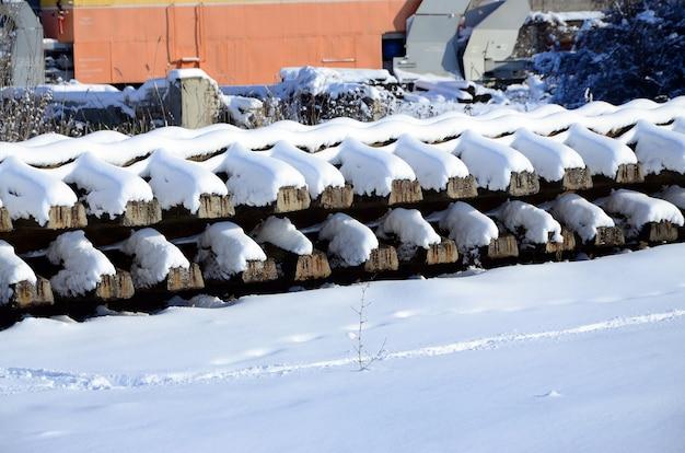 Muitos trilhos velhos e dormentes são empilhados em um armazém railway no inverno.
