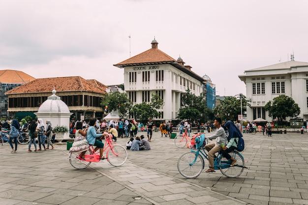 Muitos turistas estão andando de bicicleta coloridas do serviço de aluguel.