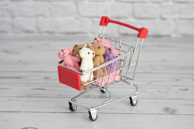 Muitos ursinhos de pelúcia de brinquedos coloridos encontram-se no carrinho de supermercado. compras no mercado. compra de presentes para aniversários e feriados.