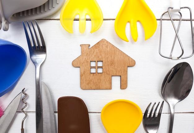 Muitos utensílios de cozinha diferentes na mesa de madeira e uma casinha de madeira entre eles