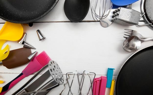 Muitos utensílios de cozinha diferentes na mesa de madeira