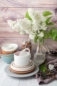 Muitos utensílios de mesa vazio diferente. buquê de lilás branco