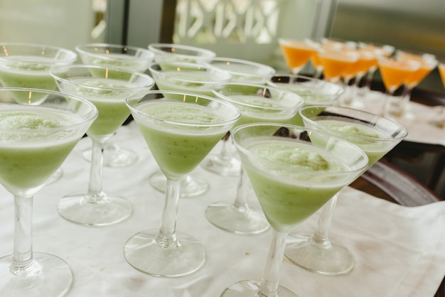 Muitos vidros do gelado prontos para ser servido por um empregado de mesa durante um casamento.