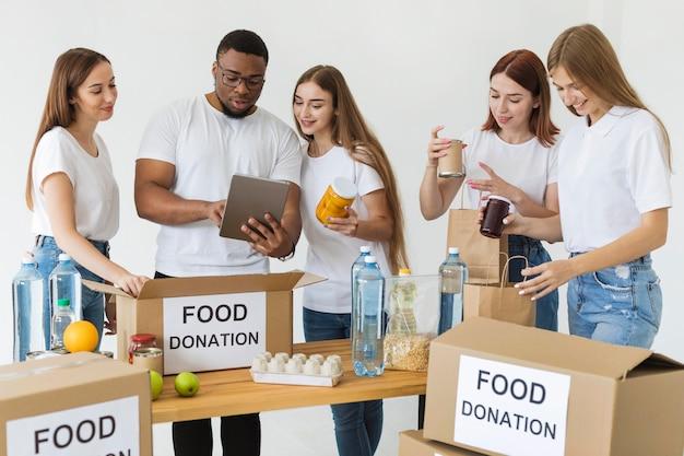 Muitos voluntários preparando caixas com doações de alimentos usando tablet